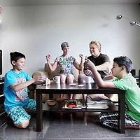 Nederland, Diemen , 12 juli 2010..Het lesbische ouderstel Marieke Kroes en Marleen Keÿlard en hun kinderen Koen (11) en Bram (9) Keÿlard - Kroes aan het kaartenspelen in hun woning in Diemen..Two lesbian mothers with their children