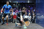 Mathieu Castagnet of France (wearing Black shirt) hits a shot against Omar Mosaad of Egypt (wearing light Blue shirt) in the final. the Final, Omar Mosaad of Egypt v Mathieu Castagnet of France , Canary Wharf Squash Classic 2016 , at the East Wintergarden in Canary Wharf , London on Friday 11th March 2016.<br /> pic by John Patrick Fletcher, Andrew Orchard sports photography.