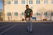 A young black male prisoner stands in one of the excercise yards inside HMP/YOI Portland, Dorset, United Kingdom.
