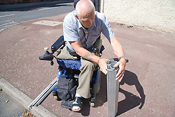 Male wheelchair user folding up a portable travel ramp after using it at a roadside kerb,