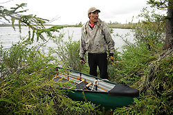 Joseph Catholique rests after carrying his canoe for 5 miles through rough terrain to avoid the rap[ids of the Thelon river. A group of Dene First Nation paddled in the Thelon Sanctuary August, 2011. It is a place ruled by the biggest and smallest--the grizzly and the mosquito--and by the extremes of sub-arctic seasons. The Thelon is the largest and most remote game sanctuary in North America, which almost no one has heard of. (Photo by Ami Vitale)Dene First Nation youth paddle down the Thelon river In the middle of the largest and most remote game sanctuary in North America, in the Northwest Territories, just south of the Arctic Circle. Its fate now hangs in the balance, protected on paper, but with little management, no money, and no voice for the Dene, its most ardent advocate for protection, while mining (for diamonds, gold, and uranium) threats, buoyed by recent prices, loom. Dene youth have rarely been deep into the Thelon, yet the caribou is still their life blood, reverentially important. These Dene are amongst the last hunter/gatherers in the Northern Hemisphere. (Photo by Ami vitale)