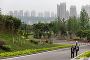Men walk through a park near an affordable housing neighbourhood in Chongqing, China, on Tuesday, April 12, 2016. The municipality of 30 million people saw state-led development approach fueled the fastest pace nationwide, with President Xi Jinping praising policy innovations that have included subsidized housing and relaxed residency rules that encourage labor mobility.