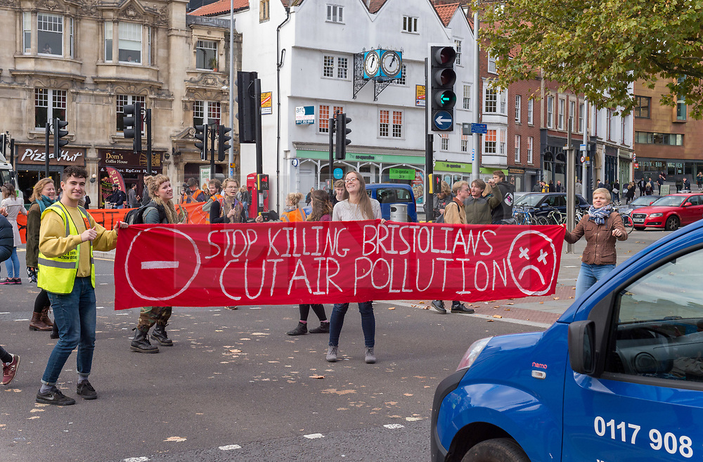 © Licensed to London News Pictures. 25/10/2018. Bristol, UK. Environmental group Extinction Rebellion stop Bristol traffic by holding a 20 minute disco in the city centre on Baldwin Street, to draw attention to the ecological crisis and climate breakdown. Police attended but there were no arrests. This latest action by the group is part of its escalating nationwide campaign to draw attention to the ecological crisis and climate breakdown, the group say using humorous, provocative and disruptive actions. Extinction Rebellion say that people need to know the severity of the climate catastrophe we are facing, that we are in the 6th mass species extinction and people are already dying, and that societal collapse and mass death are seen as inevitable by scientists and other credible voices, with human extinction also a possibility, if rapid action is not taken. Extinction Rebellion is coordinating a nonviolent uprising against what they say is criminal inaction by the British government on the climate emergency and ecological crisis. On 31st October, there will be a Declaration of Rebellion taking place in Parliament Square in London, with a series of disruptive actions planned from 12th November leading to Rebellion Day on 17th November. The group's key demands are:<br /> The Government must tell the truth about the ecological emergency, reverse inconsistent policies and work alongside the media to communicate with citizens; The Government must enact legally binding policy measures to reduce carbon emissions to net zero by 2025 and to reduce consumption levels; A national Citizen's Assembly to oversee the changes, as part of creating a democracy fit for purpose. Photo credit: Simon Chapman/LNP