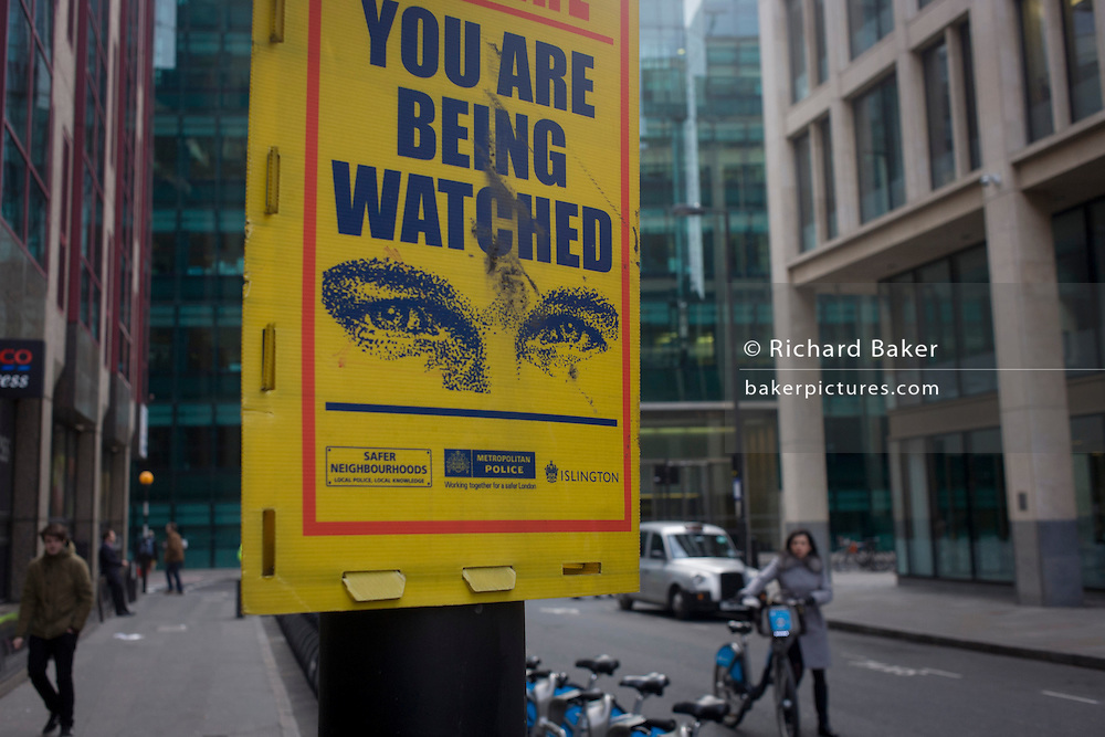 A warning sign aimed at petty criminals, telling them they are under surveillance by the Metropolitan Police, near a row of Boris bikes and passers-by. The anti-crime initiative is from the police and Islington council whose logo is at the bottom alongside the Safer Neighbourhoods organisation, wishing to cut theft and robberies.