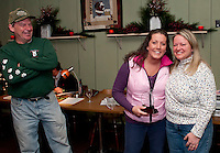 Jim Lyman looks on as Suzy Martin in presented with the Volunteer of the Year award from Diane Lyman at Christmas Island Steak House Thursday evening during registration for the 2010 Laconia World Championship Sled Dog races.  (Karen Bobotas/for the Laconia Daily Sun)