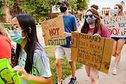 "30 JULY 2020 - DES MOINES, IOWA: A group of students walk up Grand Ave. to the Governor's Mansion in Des Moines. About 45 high school students from across Des Moines marched from downtown to the Governor's Mansion to protest Iowa Governor Kim Reynolds' proclamation ordering Iowa schools to reopen to in person classes despite the COVID-19 pandemic. The students stood in front of the mansion and chanted before staging a ""die  in"" in the street. The Governor's order mandates in person instruction rather than on line or a mix of on line and in person. Several school districts have indicated that they will disregard the Governor's orders and reopen with a hybrid system or mostly on line. The Governor will allow districts to apply for a waiver if the Coronavirus (SARS-CoV-2) infection rate is more than 15% in their community.      PHOTO BY JACK KURTZ"
