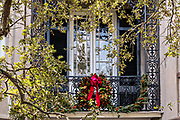 A magnolia Christmas wreath decorates the balcony of a historic home at Meeting Street in Charleston, SC.