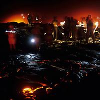 USA, Hawaii, Volcanoes National Park,  Tourists watch molten lava flow from Kilauea volcano eruption at night