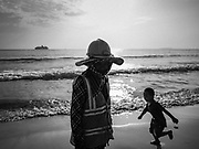 "12 FEBRUARY 2019 - SIHANOUKVILLE, CAMBODIA: A Cambodian construction worker walks past a Chinese tourist's child running down the beach near the Blue Bay resort development. Blue Bay is a Chinese casino and resort being built in Sihanoukville. There are about 50 Chinese casinos and resort hotels either open or under construction in Sihanoukville. The casinos are changing the city, once a sleepy port on Southeast Asia's ""backpacker trail"" into a booming city. The change is coming with a cost though. Many Cambodian residents of Sihanoukville  have lost their homes to make way for the casinos and the jobs are going to Chinese workers, brought in to build casinos and work in the casinos.       PHOTO BY JACK KURTZ"