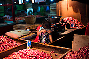 A child sitting between the vegetables at a Pasar in Surabaya arab quarter, Java.
