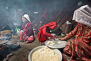 """Nemat Ullah and Woolook Bu's yurt. Women are cooking """"Borsok"""", a fried dough that will be eaten by the travellers on their journey down to the lower valleys...Daily life at the Khan (chief) summer camp of Kara Jylga...Trekking through the high altitude plateau of the Little Pamir mountains (average 4200 meters) , where the Afghan Kyrgyz community live all year, on the borders of China, Tajikistan and Pakistan."""