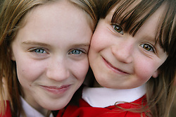 Two young girls hugging and smiling,
