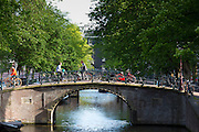 Canal and cyclists crossing one of Seven Bridges from corner of Keizersgracht and Regilersgracht in Amsterdam, Holland