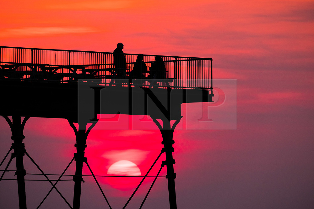 © Licensed to London News Pictures. 09/04/2019. Aberystwyth, UK. At the end of a day of broken cloud and some sunshine, the sun sets spectacularly behind the silhouette of people relaxing at the end of the seaside pier in Aberystwyth on the Cardigan Bay coast of west Wales. Photo Credit: Keith Morris/LNP