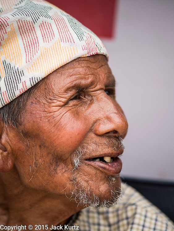 02 AUGUST 2015 - BHAKTAPUR, NEPAL:  A homeless elderly man in a small Internal Displaced Person (IDP) camp at Durbar Square in Bhaktapur for people left homeless by the Nepal earthquake. The Nepal Earthquake on April 25, 2015, (also known as the Gorkha earthquake) killed more than 9,000 people and injured more than 23,000. It had a magnitude of 7.8. The epicenter was east of the district of Lamjung, and its hypocenter was at a depth of approximately 15km (9.3mi). It was the worst natural disaster to strike Nepal since the 1934 Nepal–Bihar earthquake. The earthquake triggered an avalanche on Mount Everest, killing at least 19. The earthquake also set off an avalanche in the Langtang valley, where 250 people were reported missing. Hundreds of thousands of people were made homeless with entire villages flattened across many districts of the country. Centuries-old buildings were destroyed at UNESCO World Heritage sites in the Kathmandu Valley, including some at the Kathmandu Durbar Square, the Patan Durbar Squar, the Bhaktapur Durbar Square, the Changu Narayan Temple and the Swayambhunath Stupa. Geophysicists and other experts had warned for decades that Nepal was vulnerable to a deadly earthquake, particularly because of its geology, urbanization, and architecture.      PHOTO BY JACK KURTZ
