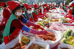 November 2, 2018 - Seoul, SOUTH KOREA - Volunteers take part in a make kimchi, a staple Korean side dish made of fermented vegetables, to donate to needy neighbors in preparation for the winter season during the Seoul Kimchi Festival at Seoul Plaza in Seoul, South Korea. Thousands of people will make kimchi with 165 tons of cabbage during the festival which is held from Nov. 2 until Nov. 4. (Credit Image: © Ryu Seung-Il/ZUMA Wire)