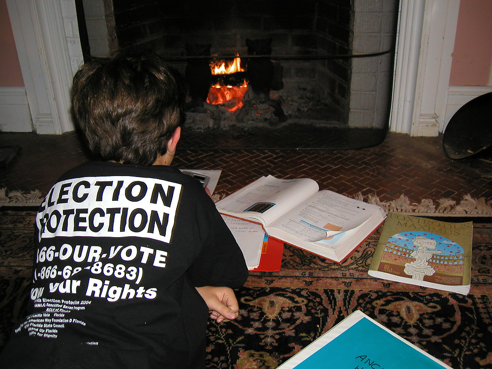 Wrapped in an Election Protection t-shirt, a young boy does homework by light of a fireplace.
