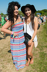 © Licensed to London News Pictures. 11/06/2015. Newport, UK. Female festival goers wearing summery dresses and hats pose for a picture at Isle of Wight Festival 2015. Today has been hot and sunny.  This years festival include headline artists the Prodigy, Blur and Fleetwood Mac.  Photo credit : Richard Isaac/LNP
