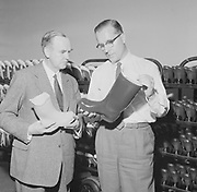 Two male factory managers examining rubber boot, Finland 1950s