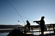 Kevin Rexford, right, casts his reel while fishing alongside Dan Doty on the Seneca Lake Pier in Watkins Glen, NY, Friday, Nov. 14, 2014.<br /> (Heather Ainsworth for The New York Times)