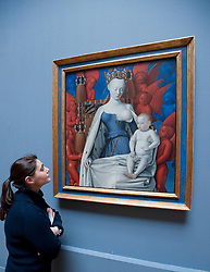 visitor looking at painting of Mary and Jesus surrounded by Seraphim and Cherubs by Jean Fouquet at Royal Museum of Fine Arts  in Antwerp Belgium