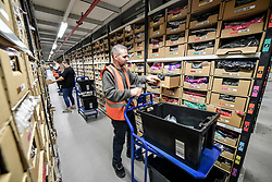 Workers pick items from thousands of clothing racks at Amazon's fulfillment centre in Swansea, in the run up to Black Friday.