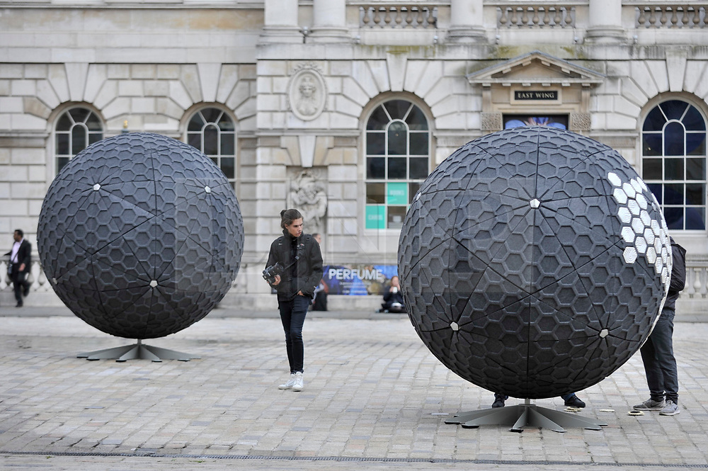 """© Licensed to London News Pictures. 19/09/2017. London, UK. An installation of giant spheres decorated with architectural tiles made from recycled from London's rubbish. Presented by Pentatonic, the machine that created the tiles is known as Trashpresso, the world's first mobile off-grid recycling plant.  The items are on display at an exhibition called """"Design Frontiers'' at Somerset House.  Forming part of London Design Festival, the exhibition showcases works from over 30 international designers. Photo credit : Stephen Chung/LNP"""
