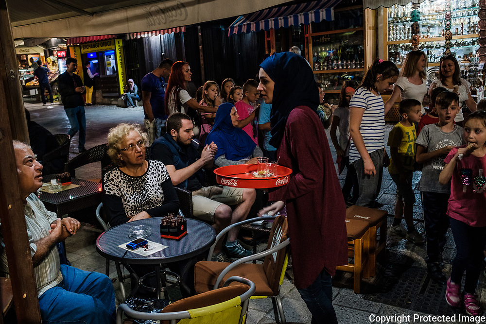 A young muslim girl waits on tourists at a cafe in the Old Town as some school kids walk by.<br /> The city continues to be a diverse mix of religions and ethnicities in-spite of it's troubled, violent past.