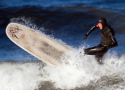 © under license to London News Pictures.  18 March, 2011. Local Saltburn surfer Evan Rogers enjoys an afternoon surfing whilst supporting Red Nose Day at a surf break at Saltburn, Cleveland. Photo credit should read Ian Forsyth/LNP