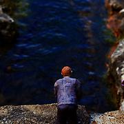 man model on bridge at bekonscot model village looking into the water.
