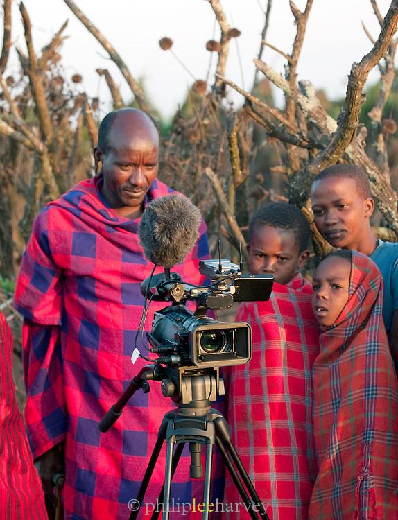 Maasai tribespeople viewing footage on a video camera, Oyaratta village near Maasai Mara National Reserve, Kenya