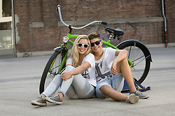 Teenage couple sitting on street with bicycle, smiling