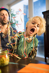 Father and son celebrate a party with paper streamers