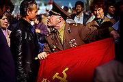 """Shouting predatel, or """"traitor,"""" a flag-waving colonel of the Soviet Army confronts one of thousands of demonstrators shouting """"Down with the Empire of Red Fascism"""" at May Day parade on Red Square in 1990. Muscovites jeered President Mikhail Gorbachev and the Soviet leadership, turning a working-class holiday into an angry display of popular discontent with Communist rule -- a movement that would lead to the dissolution of the Soviet Union in December 1991.  © Steve Raymer / National Geographic Creative"""