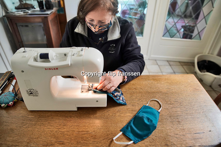 Nederland, Ubbergen, 21-4-2020  Veel particulieren, veelal al wat oudere vrouwen, naaien met hun naaimachine en stukken stof zelf mondkapjes . Hierdoor hoeven ze geen aanspraak te maken op die kapjes die voor het zorgpersoneel zo schaars verdeeld zijn . Zelf doen, maken, het geeft een gevoel van veiligheid en bescherming . Foto: Flip Franssen