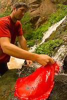 A young man fills a water bag while backpacking the Virgin River Narrows in Zion National Park, Utah.