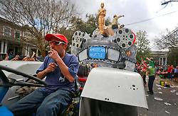 02 March 2014. New Orleans, Louisiana.<br /> Mardi Gras. A tractor driver reaches for a smoke as he pulls float riders at the  Krewe of Thoth parade in Uptown New Orleans.<br /> Photo; Charlie Varley/varleypix.com