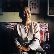 I grew up in Hue.  My parents passed away when I was three years old, and I had to live with grandparents.  At that time, my family was a rural family, and we were too poor, and so when my parents got sick they couldn't get medicine.<br /> <br /> In 1945, when the war with France began, I was living in the small village.  Many in the village wanted to fight in the war, and so I joined, too.  I was 14. I didn't go to school, but when I joined the war, in the evening, they taught me.<br /> <br /> You see, that time in Vietnam was very difficult because France was there, and Vietnam's government was terrible, and the people were very poor.  Many people had lost their children, and I had lost my parents when I was three, so I wanted to join the war.<br /> <br /> During the French War, I made mines and planted them.  After that, I worked to organize other women to join the war, too.  The women had anger, had pride, had their health, and so they wanted to join with the soldiers to fight.<br /> <br /> When I was nineteen, I got married and had my son.  And when I was twenty - my son was just six months old - my husband died.   When my son was 15, he joined in the American War with me.  One day, the soldiers were taking their guns to go out to Hue, and the American soldiers surrounded my son and shot him.  I lost my son.  And my husband was dead, too.  Everything that I loved is gone.<br /> <br /> Nguyén Thi Hiêp, born in 1930, photographed in her family room in Hue, Vietnam.  July 2010.