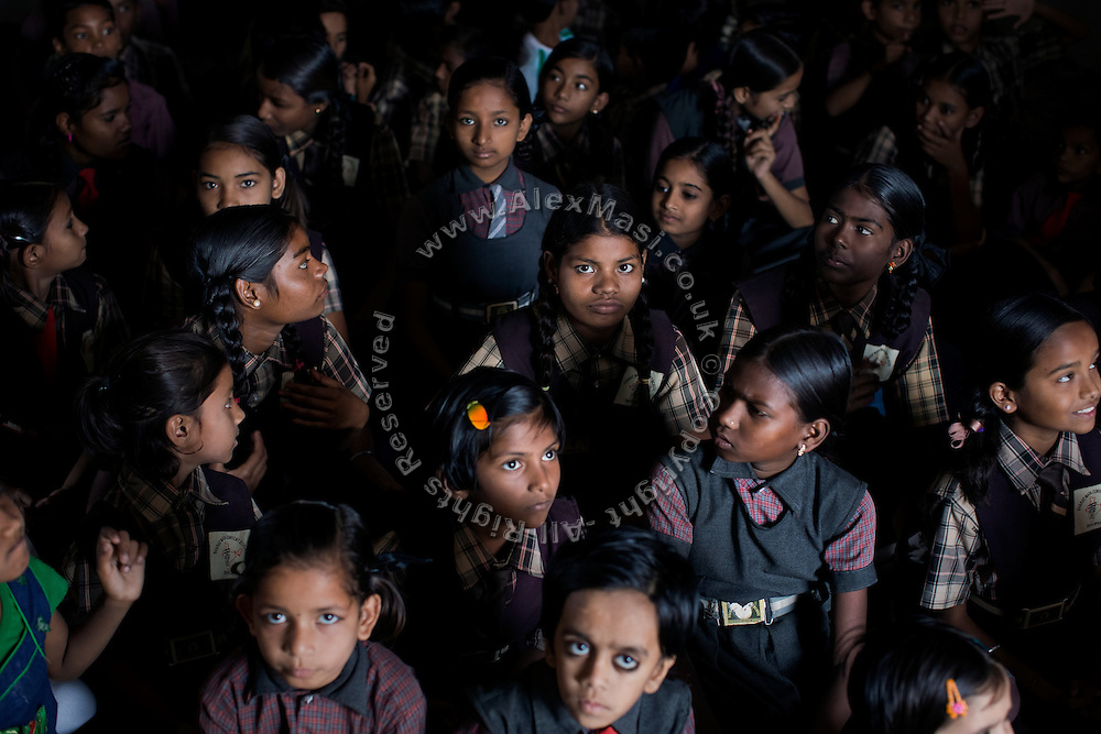 Poonam, 12, (centre) is sitting with her sister Jyoti, 13, (left) on the floor of the cozy, private school they regularly attend since 2011, located by their newly built home in Oriya Basti, one of the water-contaminated colonies in Bhopal, central India, near the abandoned Union Carbide (now DOW Chemical) industrial complex, site of the infamous '1984 Gas Disaster'. The two girls are studying in Year 6, out of 12, in 2015-16.