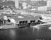 """Ackroyd_18973-3. """"LeBeck & Son. Aerials moving warehouse onto barge. August 2, 1974"""" (south Waterfront area south of the Hawthorne bridge. They are barging the entire 45,000 square feet Multnomah Plywood factory to its new home in St Helens.)"""