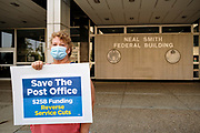 25 AUGUST 2020 - DES MOINES, IOWA: A woman pickets the Neal Smith Federal Building in Des Moines. About 100 people, postal workers and members of the public, came to the Neal Smith Federal Building Tuesday to call for increased spending for the US Postal Service and an end to attacks on the USPS by members of the Trump administration. The rally was a part of a series national rallies organized by the American Postal Workers Union (APWU). Many of the people at the rally expressed concerns that the President's actions versus the USPS could harm their ability vote by mail in the November general election.     PHOTO BY JACK KURTZ