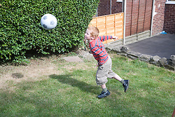 Little boy playing football in the garden,