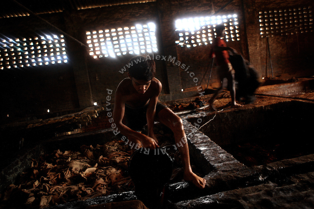 A boy is removing contaminated water from a bath after the process of liming, the removal of hair and impurities with the use of water and various agents, in an illegal tannery unit inside Jajmau, Kanpur, Uttar Pradesh. Children are largely employed to work on scraps, or little pieces of skin, like the head and the ears of the animal, which will become a small bag, a wallet, or maybe a cheap phone leather case.