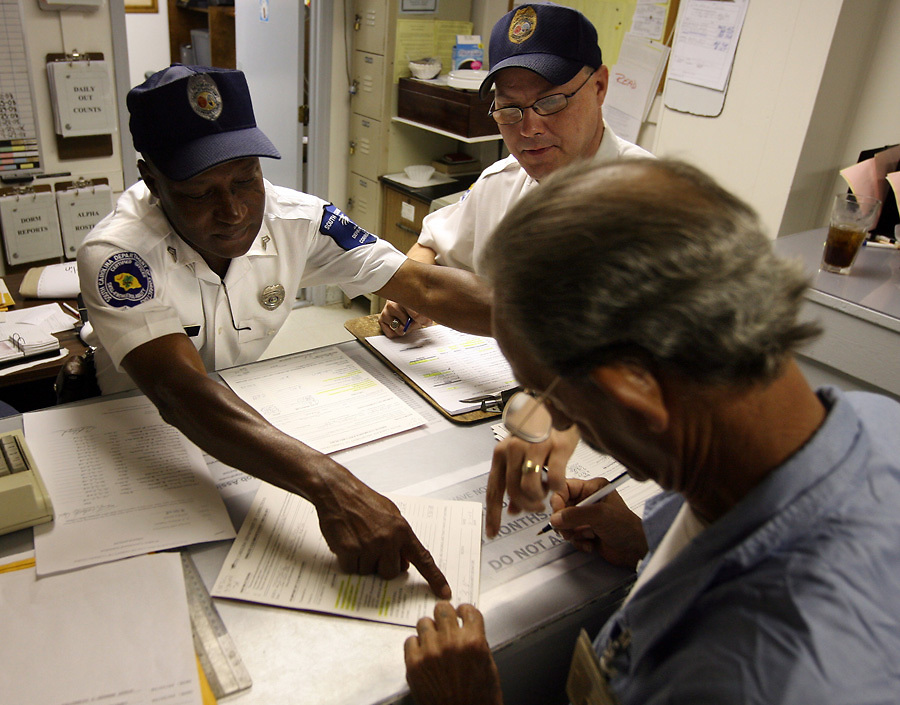 """Correctional Officer's SGT K. Oliver, left, and Lt. David Vick show inmate Roger """"Pop"""" Smith, 60, where to sign his release paperwork before being released from prison."""