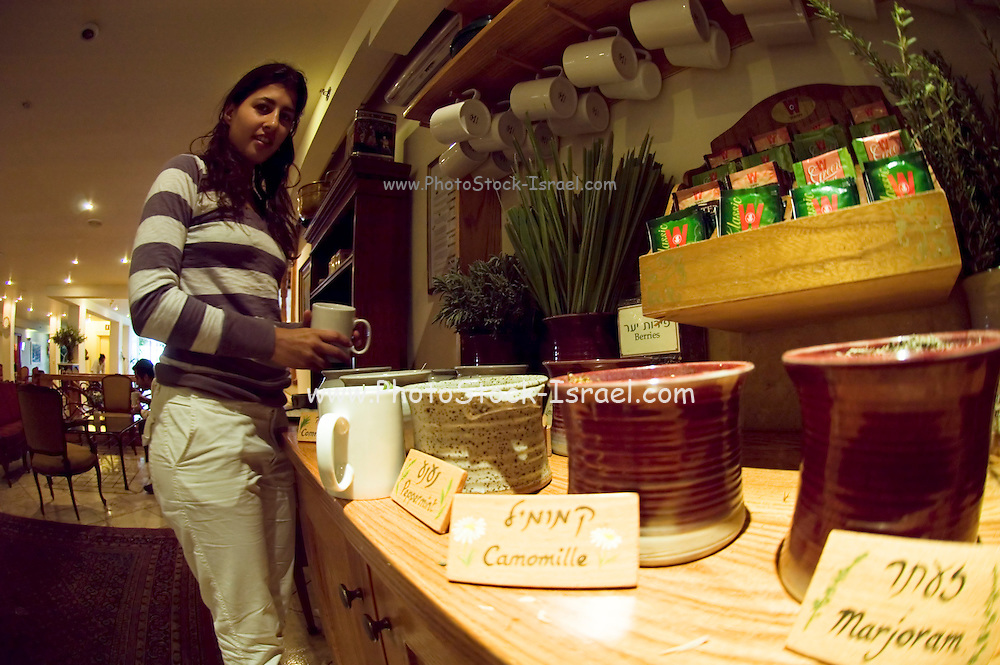 Interior shot of a young woman Making herself a cup of herbal tea. Wide angle view. Model Release Available