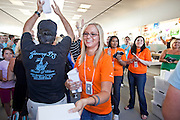 12 JUNE 2009 - SCOTTSDALE, AZ: An Apple Store employee hands out tee shirts to people coming into the store during its grand opening Friday. The outlet will be Arizona's largest Apple Store, occupying nearly 10,000 square feet in the Outdoor Lifestyle Center in the Scottsdale Quarter. The store, the fifth in the Phoenix area, uses a radically different design from other Apple Stores in some respects, ceilings in the building are approximately 20 feet high, and lined with a 75-foot long skylight, reducing dependence on artificial lighting. Aiding the skylight is an all-glass front and rear, permitting visitors to see directly through the store. PHOTO BY JACK KURTZ