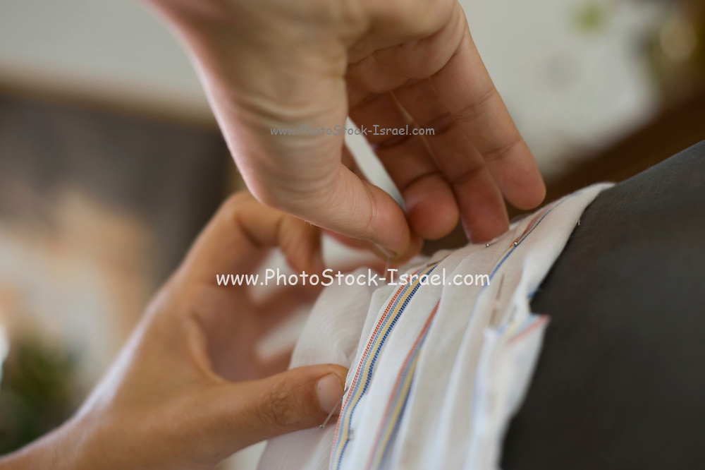 close up of a woman sewing a dress on a tailor's dummy