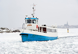 Passenger ferry sailing through sea ice to  village of Fiskebackskil during cold winter 2010 on Bohuslan coast in Vastra Gotaland Sweden