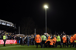 Fans on the pitch are confronted by police and stewards after the game