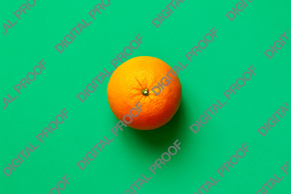 Fresh orange fruit isolated on green background viewed from above, flatlay style.  Close-up.